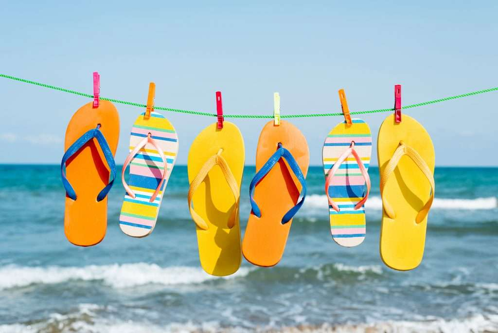 closeup of some different pairs of colorful flip-flops hanging on a clothes line on the beach, with the sea in te background