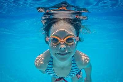 Kid having fun in swimming pool. Underwater portrait of child. Summer vacation